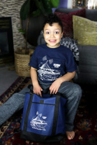 boy in kxrw shirt with tote bag
