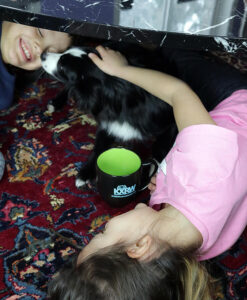 two kids and a dog with kxrw mug on the floor