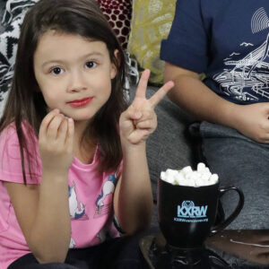 little girl with peace sign with kxrw mug